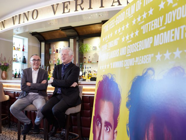 """Yesterday"" director Danny Boyle (left) and scriptwriter Richard Curtis relax before a press conference in the Pier Hotel's wine bar In Vino Veritas."